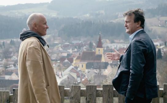 Der Impfgegner Klaus Bielau im Gespräch mit Hanno Settele. Im Hintergrund ein Dorfpanorama